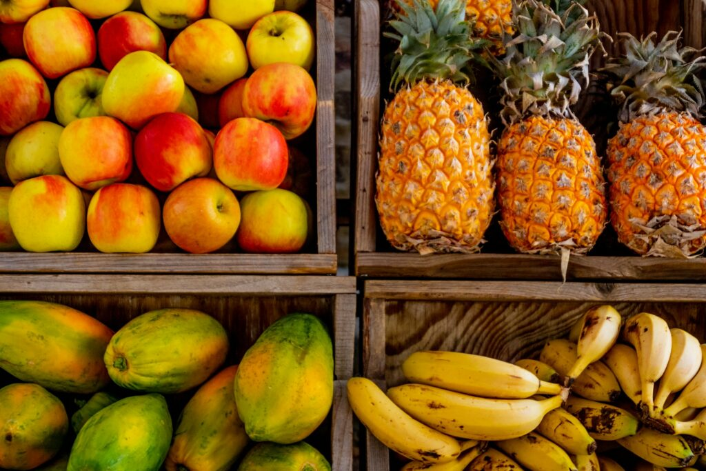 Apples, pineapples, papayas and bananas in fruit boxes