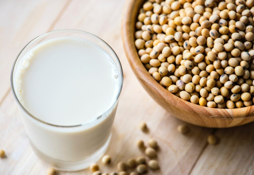 Soy milk in a glass and soy beans in a wooden bowl.