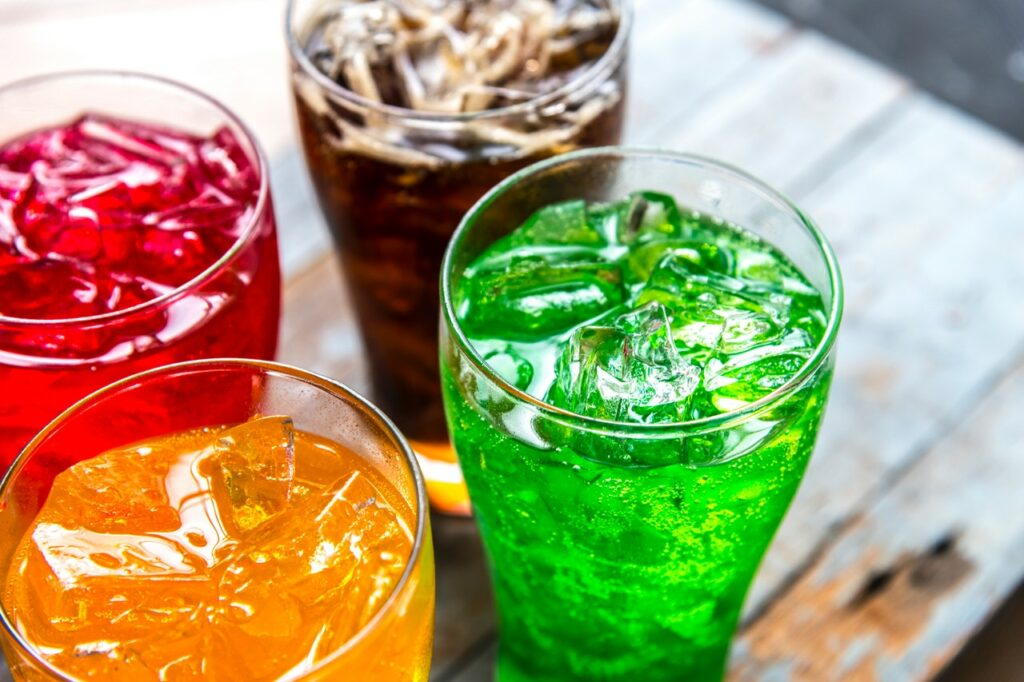 red, brown, yellow and green coloured liquids in glasses with ice cubes