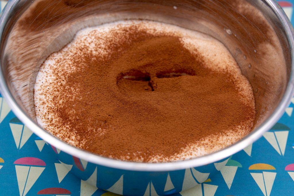 Das Kakaopulver über den Schnee sieben und unterheben