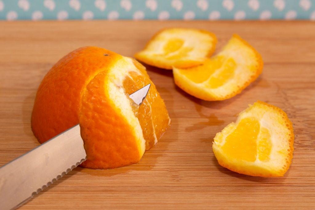 Die Orange halbieren und die Schale in Streifen samt der weißen Haut abschneiden.
