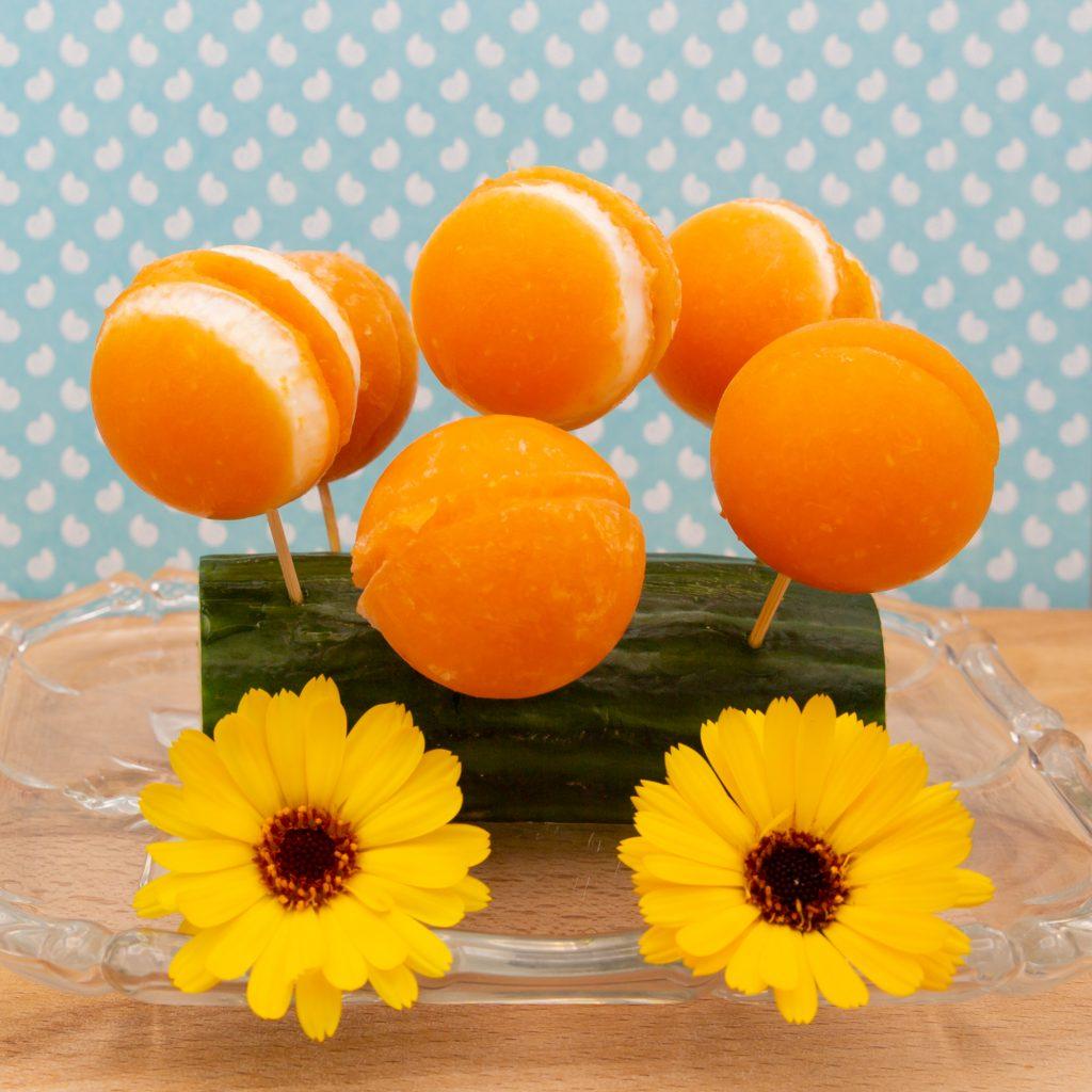 Eis-Pops aus Möhren-Orangen-Eis zum Teil mit Schichten aus Joghurt-Eis