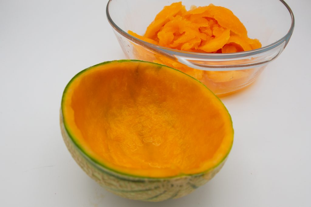 Mit einem Esslöffel wird das Fruchtfleisch der Melone ausgekratzt bis ca. 1 cm Schale übrig bleibt.