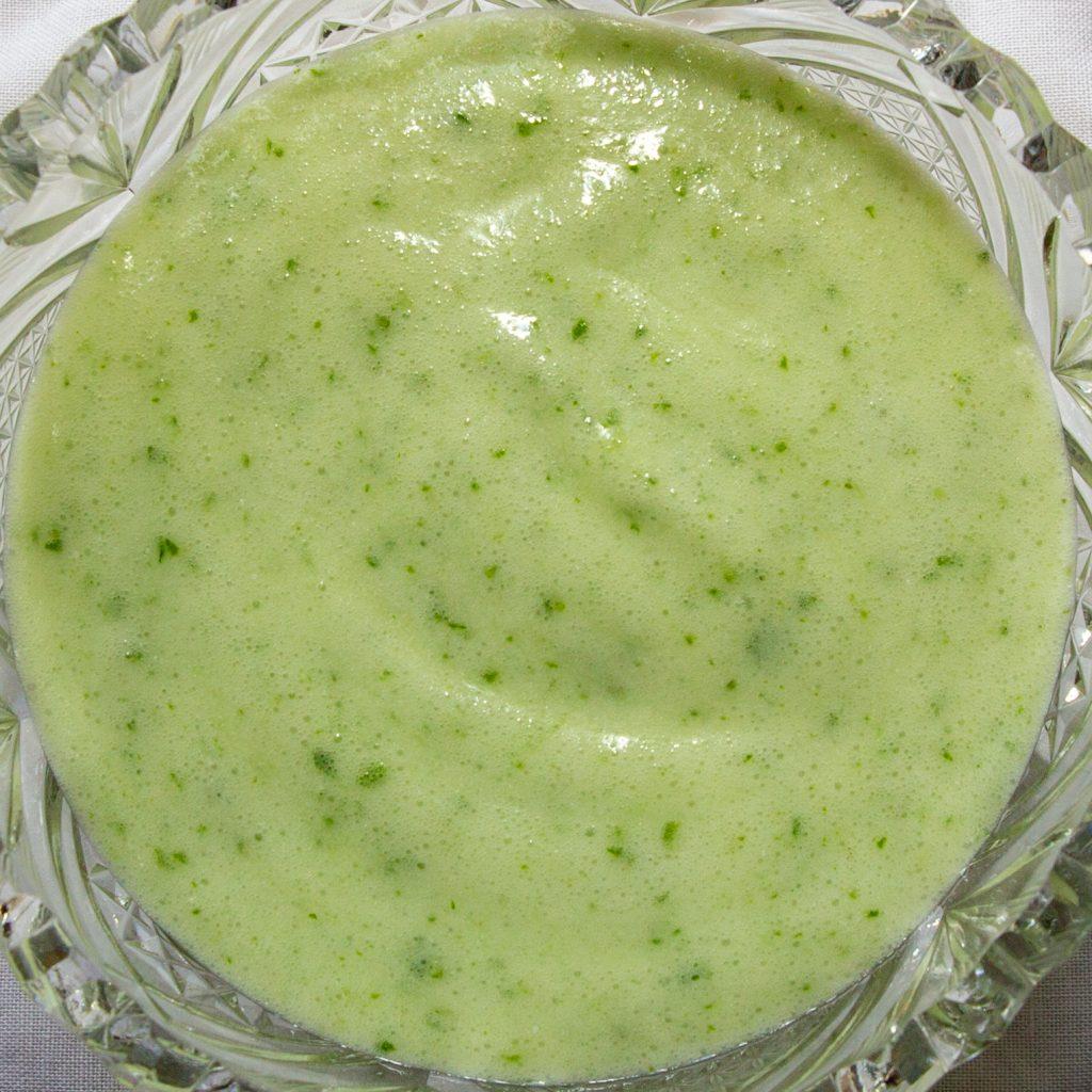 Für das Basilikum-Eis wird das aufgeschlagene Aquafaba unter das Basilikum-Kokos-Püree gehoben und in Dessertschalen gefüllt.