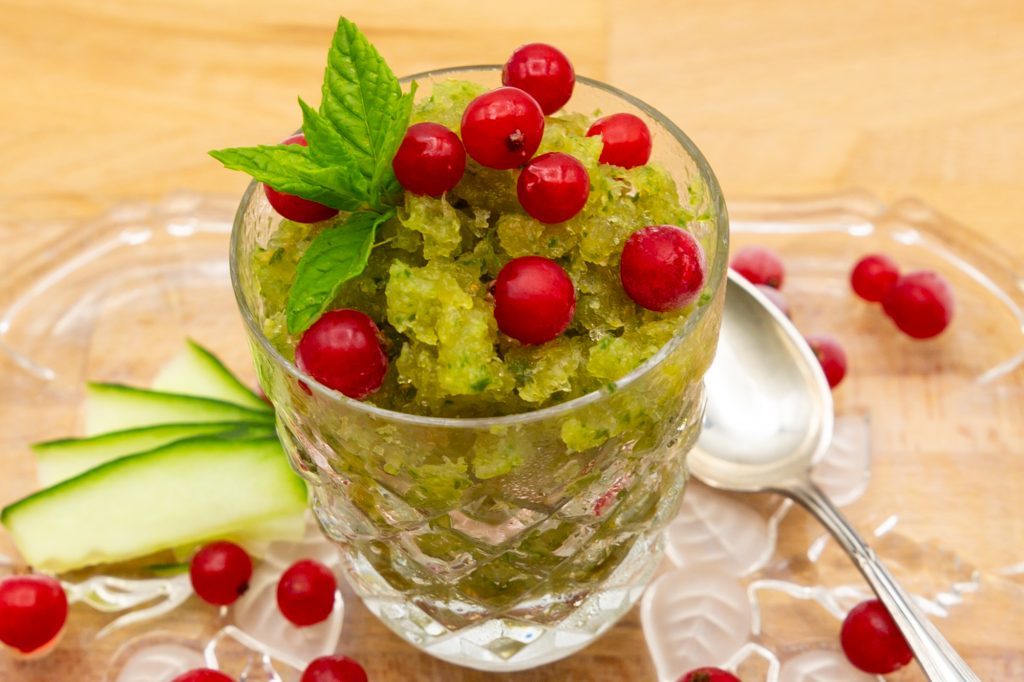 Cucumber ice cream as granita decorated with currants, mint and cucumber.