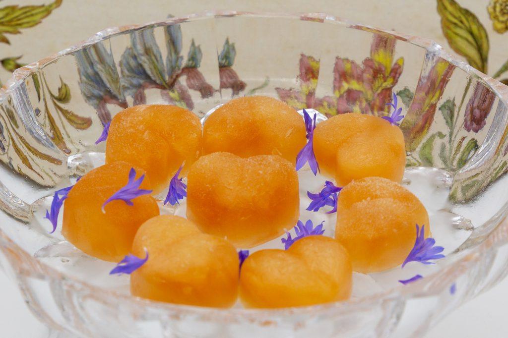 Grapefruit-Sorbet wie hier in Pralinenherzformen eingefroren ergibt ein hübsches Arrangement mit Kornblumenblüten.
