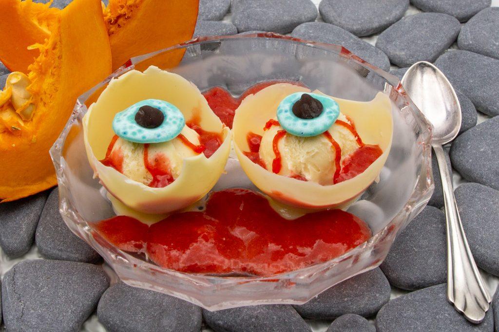 Creepy vanilla ice cream eyeballs with strawberry sauce as Halloween dessert.