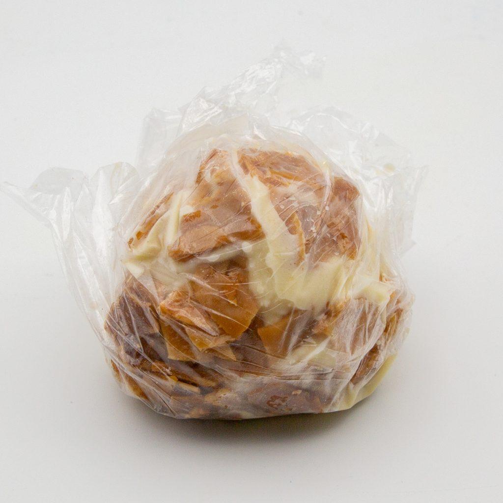 Kugel Bienenstich-Eis mit Mandelkrokant in Folie gehüllt.
