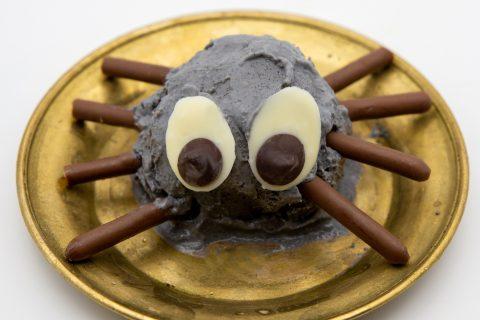 Die fertig Spinne mit Beinen aus Mikadostäbchen und Augen aus weißer und dunkler Schokolade.