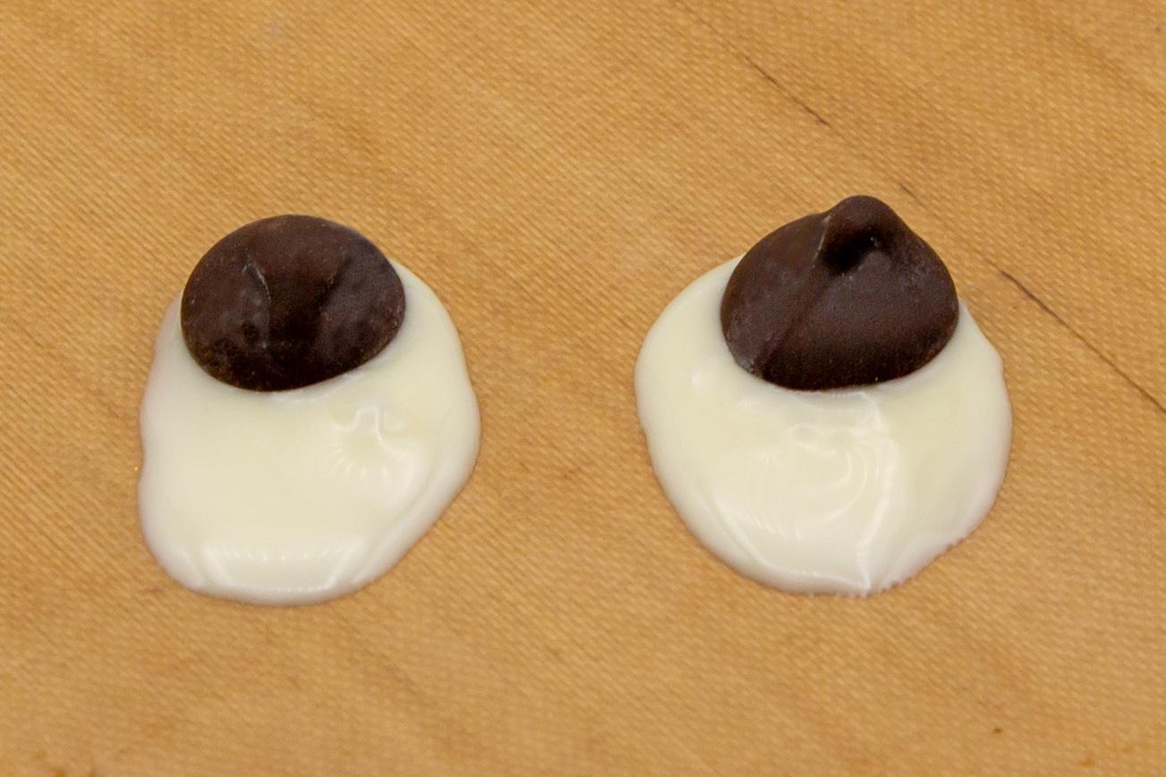 Für die Augen wird auf Backpapier ein Oval mit weißer Schokolade aufgetragen und einen dunkler Schokodrops reingesetzt.