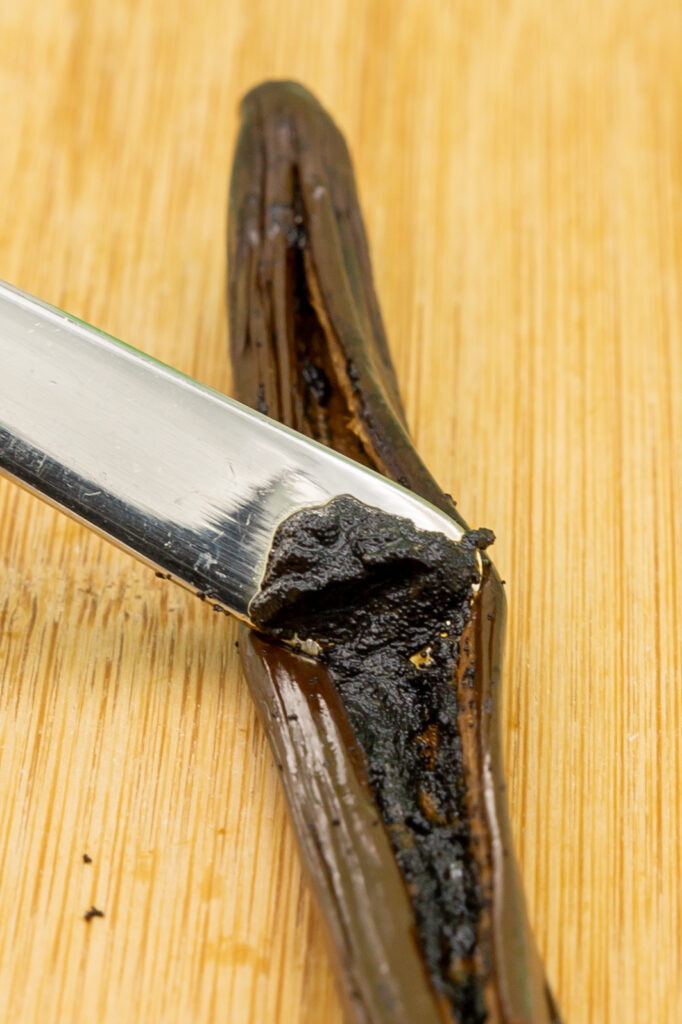 Scrape the vanilla pulp out of the pod with a spoon handle. The picture shows a special vanilla pod (Vanille bleue), therefore the pulp appears very moist.