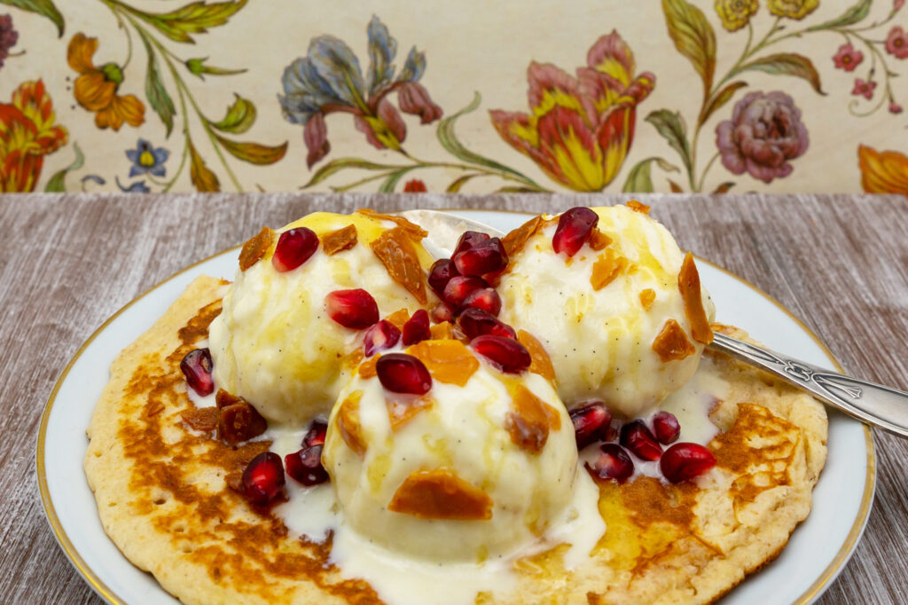 Creamy cashew ice cream on pancake with caramelized nuts, honey and pomegranate seeds.