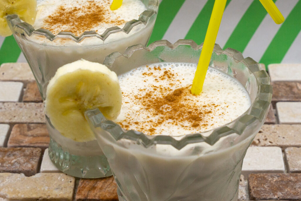 Delicious vegan banana milkshake sprinkled with cinnamon and decorated with banana slice.