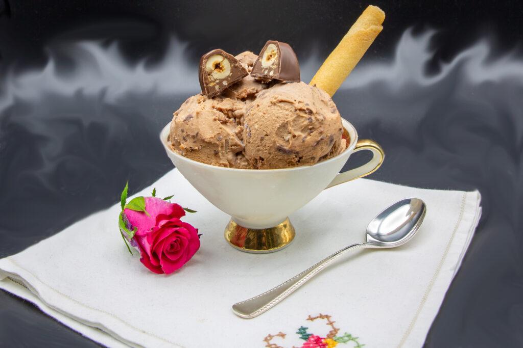 Bacio-Eis angerichtet mit einer halbierten Schokonuss-Praline und Waffelröllchen.