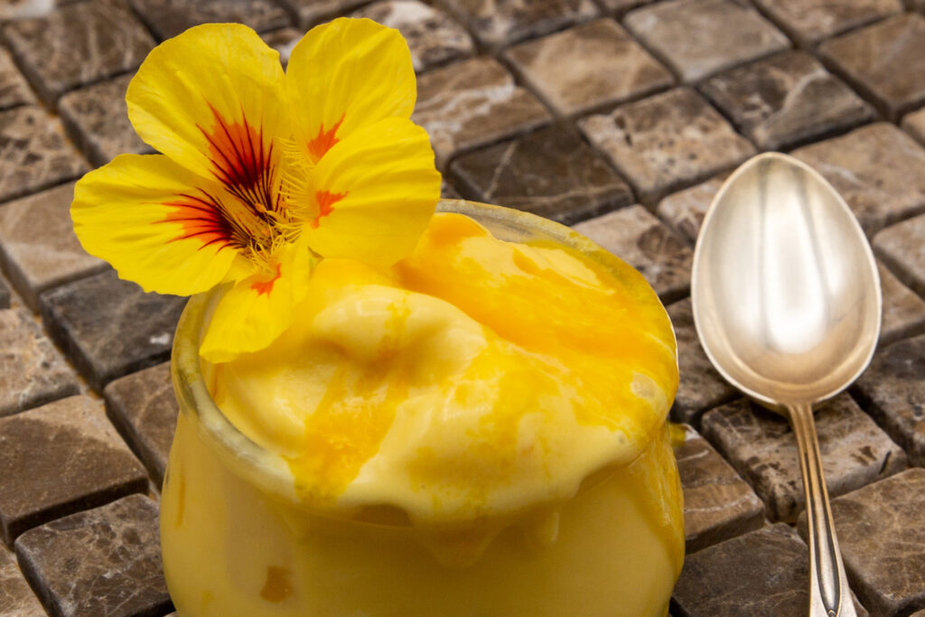 Creamy mango ice cream - here decorated with a beautiful capuchin flower. These flowers are edible.